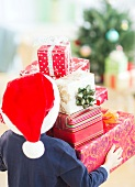 Boy (6-7) carrying christmas gifts
