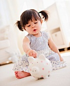 Baby girl (12-17 months) playing with piggy bank