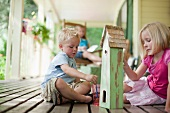 Brother and sister painting birdhouse together