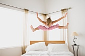 Girl (12-13) jumping on bed