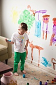 Toddler boy (2-3) painting on wall
