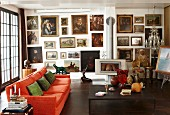 Large gallery of oil paintings in living room with orange couch, antiques, crystal chandelier and log burner