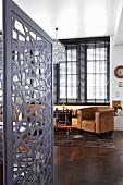 Blick in Arbeitszimmer mit grauem Paravent aus Metall, dunklem Edelholzparkett und braunem Ledersessel