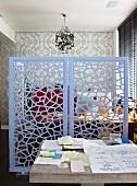 Rustikaler Arbeitstisch neben filigranem, pastellblauen Raumteiler aus Metall; dahinter eine Wandtapete im Retrolook