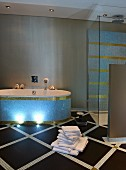 Elegant bathroom with pastel blue and gold mosaic tiles on bathtub and walls; tiled floor with diamond pattern