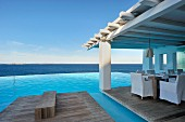 Infinity pool and seating area on roofed wooden deck with sea view