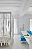 Himmelbett mit aufgehängten Bändern in weißem Schlafzimmer mit Holzdecke und mediterranem Flair