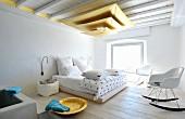 Hängeleuchte aus goldfarbenen, übereinander gehängten Segeln in mediterranem Schlafzimmer mit Bauhaus Schaukelstühlen vor Doppelbett