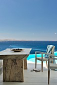 Rustic table and white wicker chairs on terrace next to pool with view of sea
