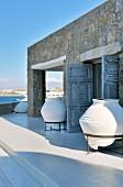weiße Amphoren im Metallgestell auf Terrasse