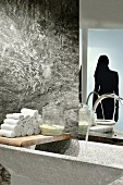 Stone trough and towels on vintage wooden board against stone wall with silhouette motif of woman on glass door