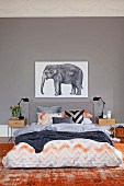 Interesting colour scheme in shades of grey and faded brick red; double bed with illustration of elephant above headboard