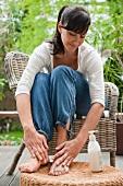 Woman rubbing cream into her feet