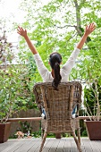 Woman sitting on garden chair with arms stretched out on terrace