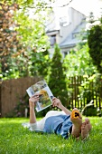 Woman lying on garden lawn reading magazine