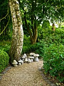 Gravel path & stone mushroom ornaments in garden