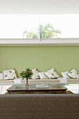 Back of couch in front of table and bench with seat cushions against green-painted wall with long transom window