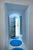 Blue, circular rugs in narrow corridor with open batten door at one end