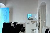Raum mit einer blauen und einer weissen geöffneten Holztür; Tierfelle auf Möbeln im Vordergrund