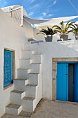 Blue door and lattice window in North-African courtyard with masonry samba staircase leading to roof terrace