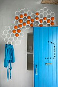 Perforated frames on wall used for decorative orange storage; open door and apron in matching turquoise blue