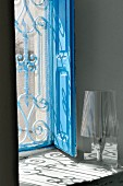 Window recess with blue wooden shutters and pattern of light cast by grille
