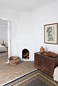 Simple, Moroccan interior with modern painting above old wooden trunk and masonry fireplace in corner