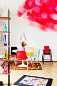 Retro-style interior with round dining table, colourful plastic chairs, baby's play mat & high chair