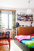 Colourful bedroom with double bed, cot & wall-mounted shelves