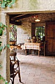 View through open doorway; vintage, terracotta veranda floor and baskets on table in front of barred window opening in stone wall