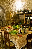 Dishes of vegetables and fruit next to tray of vinegar and oils bottles on table in front of bottles of wine on shelving in rustic dining room