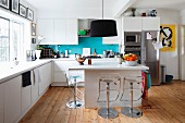 Pendant lamps with black lampshades above modern island counter in open-plan kitchen with barstools on wooden floor