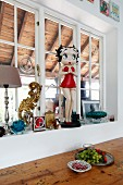 Plastic 'Betty Boop' statue on windowsill of lattice window above platter of fruit on wooden table