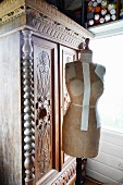 Vintage tailors' dummy in front of antique, 19th century cupboard of carved wood in corner