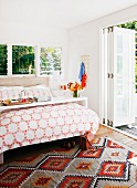 Double bed with overbed table in sunny room with open folding door leading to garden terrace; ethnic-style woven rug on floor