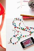 Selbstgebastelte Kette mit gemalten Anhängern & Handy mit gespeicherten Kinderkunstwerken