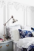 Nostalgic double bed with ruffled lace pillows against white wall with Baroque ornamentation; chromed, angle-poise lamp on bedside table