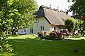 Gepflegter Rasen und Blumenbeete im Garten eines reetgedeckten, restaurierten Landhauses