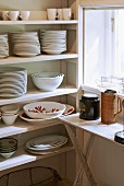 Crockery on simple kitchen shelves next to window