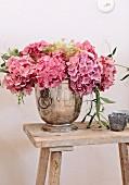 Pink hydrangea flowers in silver vessel on rustic wooden stool