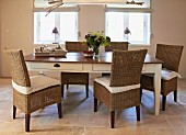 Rattan chairs around country-house table with white base and dark top
