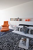 Minimalist bedroom with black and white patterned bedspread, long bookshelf in niche and orange designer swivel chair