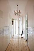 Elegant, narrow hallway with chandelier, half-height tiled walls and rustic wooden floor