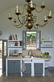 Brass chandelier in white kitchen with grey unit doors and window grille