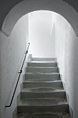 Rounded arch leading to old staircase with iron handrail