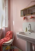 Pedestal washbasin with tiled splashback below mirror hung on pink wall next to wire mesh chair in corner of room