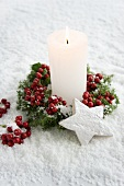 Candle with holly berries and wooden star in snow