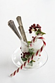 Holly berries, cutlery and candy cane in ice goblet