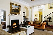 Various items of traditional upholstered furniture in front of roaring fire in open fireplace in English stately home