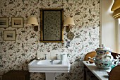 Pedestal sink and mirror on floral wallpaper; porcelain bowl on antique washstand to one side